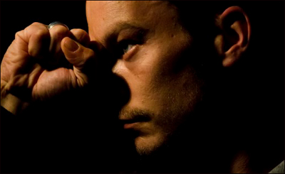 Picture of man looking depressed with clenched fist in shadow.